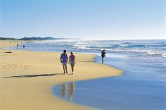 Couple walking on Coolum Beach, Queensland.