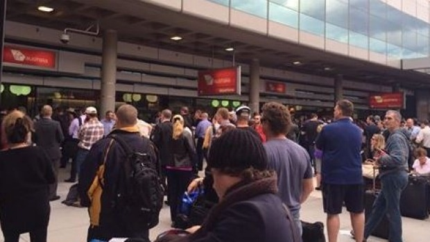 Passenger wait outside the terminal after being evacuated.