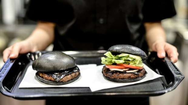 The Kuro Pearl, left, costs 480 yen and comes with black buns and cheese smoked with bamboo charcoal and black sauce ...