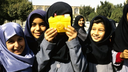 Iranian schoolgirls play with a toy camera.