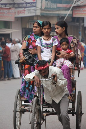 A family outing via a rickshaw. The young girl looks straight into the camera. Life is taking her forward while the ...