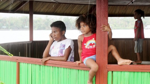 Children watch wooden boats take the group away from a rainy Assey Island in the middle of Lake Sentani, Jayapura, West ...