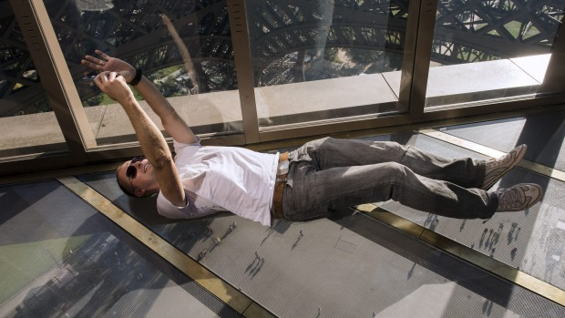 A tourists goes to great lengths to take a selfie on the new glass floor at the Eiffel Tower in Paris.
