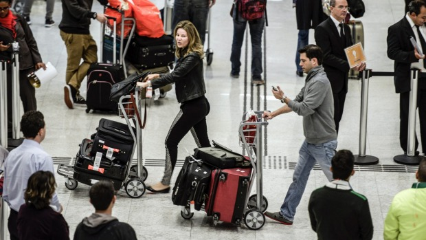 Passengers arriving from the US walk with their baggage through Terminal 3 of the Guarulhos International Airport in Brazil.