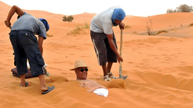 Sun and sand of a different kind: A tourist takes a sand bath in the dunes of the Merzouga desert in southeastern Morocco.