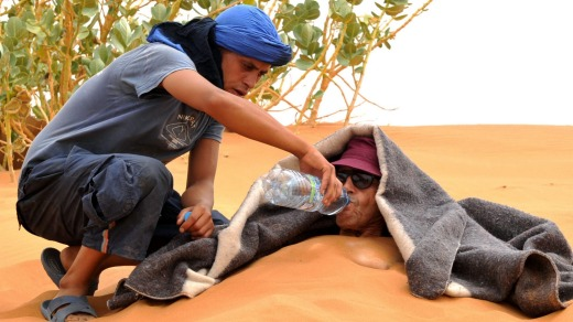 A tourist is served water as he takes a sand bath in the dunes of the Merzouga desert.