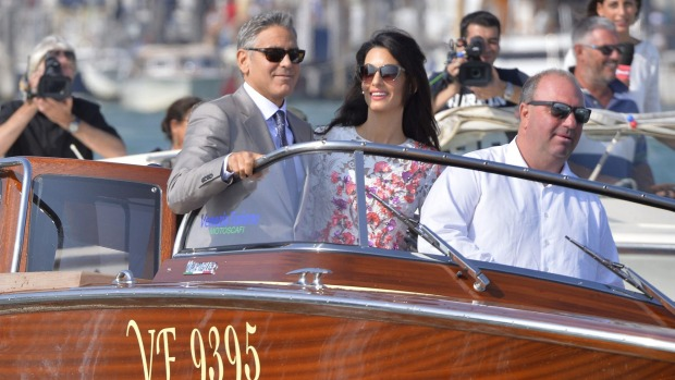 US actor George Clooney and his wife Amal Alamuddin stand on a taxi boat in Venice.