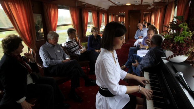 Passengers enjoy piano music in the bar car as the Tehran-bound train leaves Budapest.