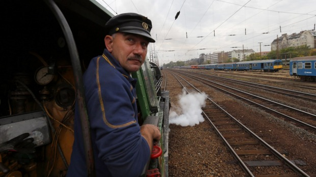 A train engineer looks out of a historic steam locomotive as it pulls the luxury Tehran-bound train into Nyugati ...
