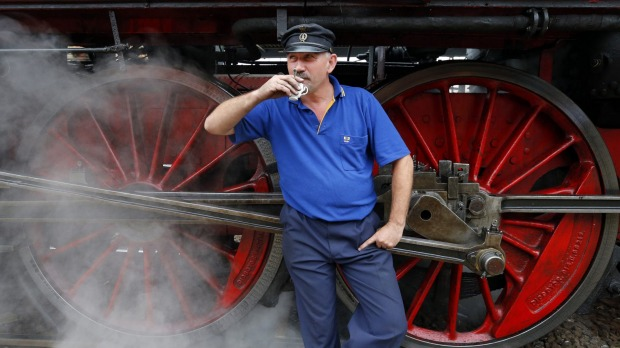 Taking a break: A train engineer enjoys a cup of coffee in front of an historic steam locomotive of a Tehran-bound train ...