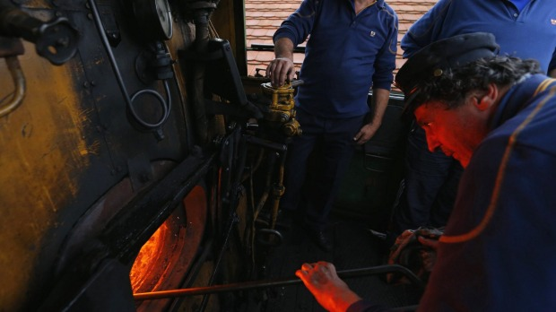 A train engineer loads a historic steam locomotive with coal as it pulls a Tehran-bound train into Nyugati Terminus in ...