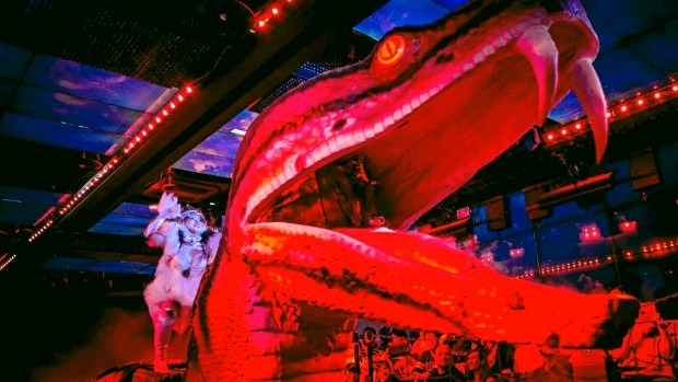 A dancer rides a large robotic snake during a show at The Robot Restaurant in Tokyo, Japan.
