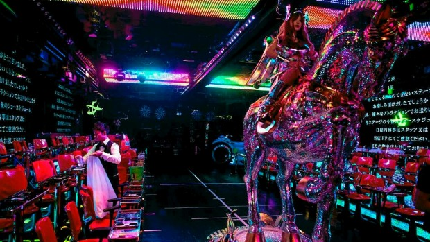 A man cleans up the stage after a show as a large robotic horse is moved back into position after a show at The Robot ...