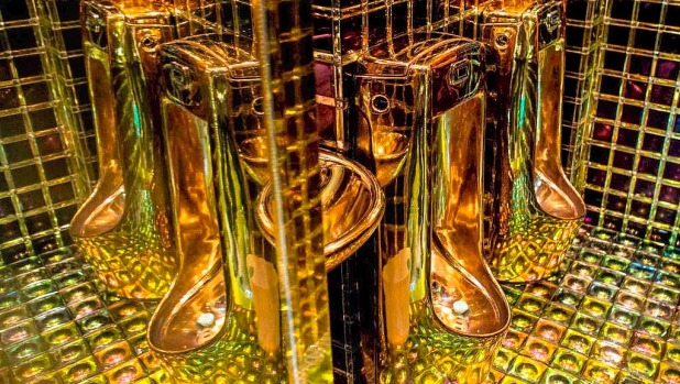 Gold coloured urinals are seen in the mens bathroom  at The Robot Restaurant in Tokyo, Japan.