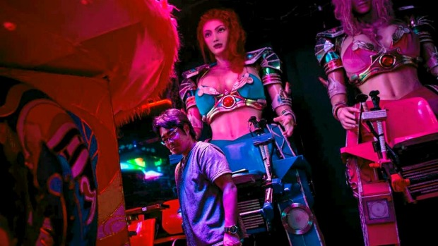 A staff member works to prepare two large female robots prior to the start of a show at The Robot Restaurant in Tokyo, Japan.