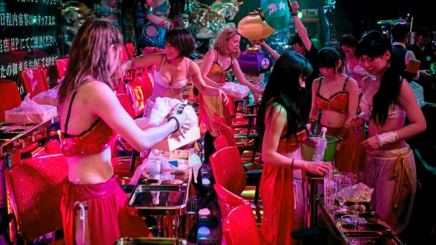 Dancers and performers work to clear garbage in between shows at The Robot Restaurant in Tokyo, Japan.