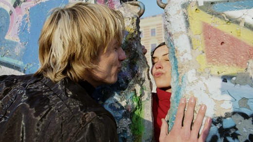 No stopping love: A couple blow kisses to each other through the mural-covered remains of the Berlin Wall.