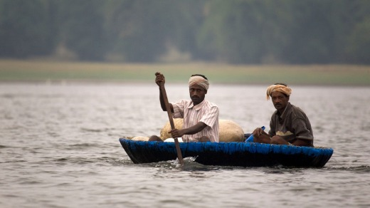 Fishermen paddle a traditional round coracle boat.