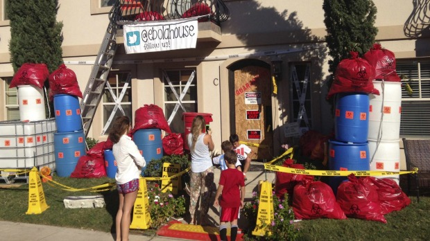 People visit a home decorated for Halloween to resemble an Ebola hot spot is seen in University Park near Dallas, Texas.