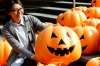 A visitor poses for a photo in an installation consists of 500 pumpkin lights to mark the Halloween in Shenyang, ...