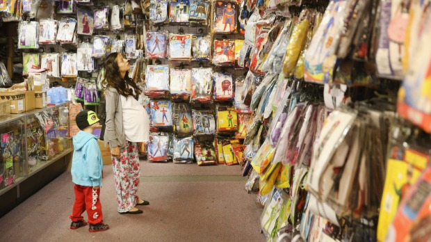 Mother and son shop for a Halloween costume at Fantasy Costumes in Chicago, Illinois.