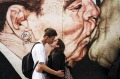 Life imitates art: A couple kiss in front of Russian painter Dimitri Vrubel's most famous work My God, help me to ...