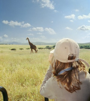 Surperb sighting: A teenage firl watches a giraffe while on a safari.