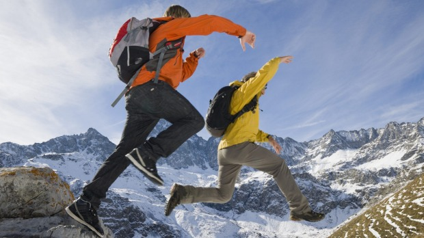 Taking risks: Two hikers jump from a rock onto a snowy slope.