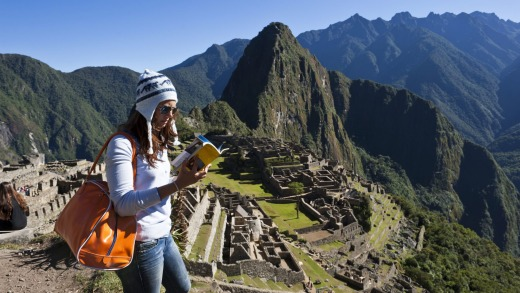 Looking deeper: A young tourist reads a guide book at Machu Picchu.