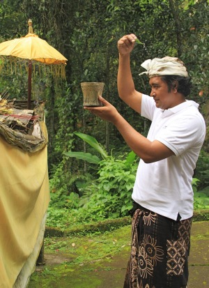 Tour guide sprinkles himself with holy water at the meditation caves.