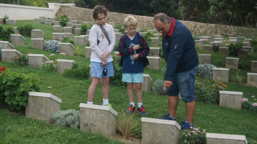 Guide Aykut tells Jake, 12, (left) and Sebbie, 10, the story of one of many Australians buried in a cemetery.