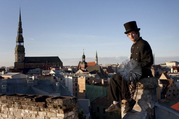 Number 5: Latvia. Pictured, a chimneysweep sitting on the chimney over the city, Riga.