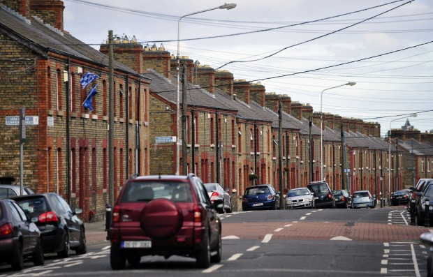 An automobile passes a row of brick terraced houses in Dublin, Ireland.