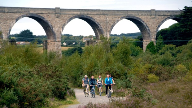 Cyclists pass the Carnon Viaduct on the Cornwall Coast to Coast cycling trail linking both Cornish coasts Cornwall UK.
