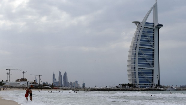Tourists enjoy the beach in front of the luxury Burj al-Arab Hotel at Jumeirah area in Dubai.