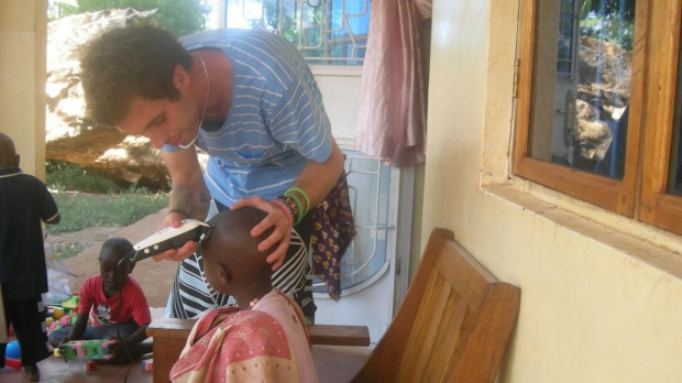 Helping hand: Nathan Bennett, from Melbourne, shaves a boy's head  during his  time as a volunteer at an orphanage in ...