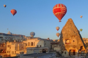 This photo was taken at dawn from our hotel balcony in Goreme, Turkey in  August 2014.  We were given a cup of coffee, and were rugged up against the cold.  Our room was in the fairy chimney in the picture.  Some of the balloons were so close we waved to the people in the baskets.  There were hundreds of balloons.  It was an amazing sight. The early morning light was beautiful.  One of the highlights of our holiday in Turkey.