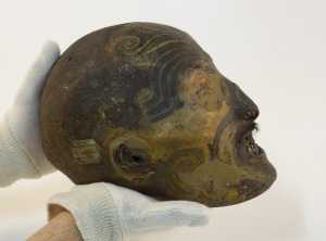 An employee displays a 19th century mummified Maori head conserved in the reserve collection of the Musee des Confluences.