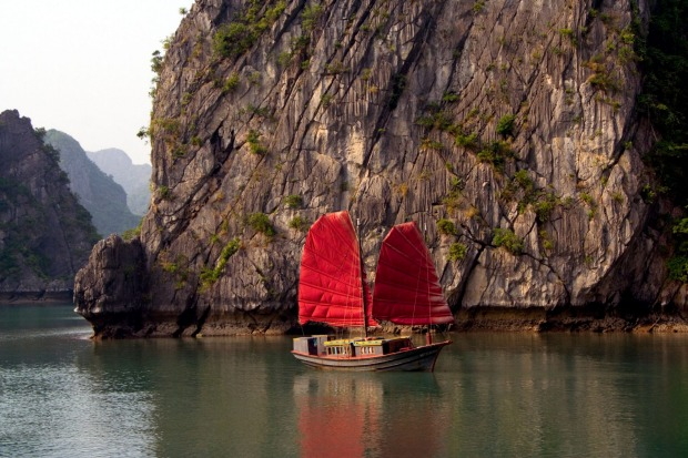 A junk sails past limestone karst mountains in Ha Long Bay.