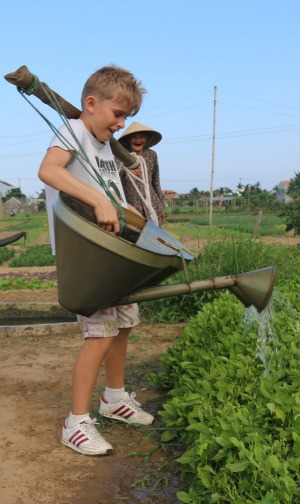 When in Rome... The children try their hand at tending the crops.
