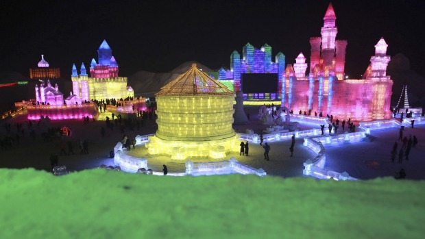 People visit newly-built ice sculptures illuminated by coloured lights during a trial operation of the 16th Harbin Ice ...