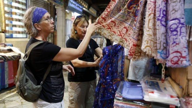 Tourists look at scarves at a market in the Omani capital Muscat. From desert camping to luxury hotels, turtle-watching, ...