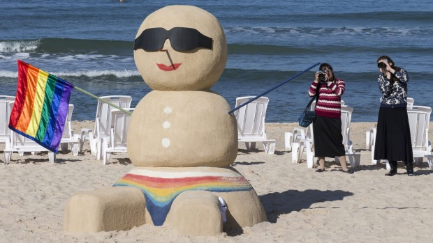 Women take pictures of a sand sculpture of a snowman standing three metres high and holding a rainbow gay pride flag at ...