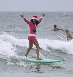 British traveller Dabriella Quayle rides the waves while celebrating Christmas Day at Bondi Beach in Sydney.