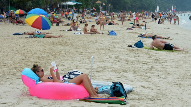 Foreign tourists relax at Patong beach in Phuket province, Thailand.