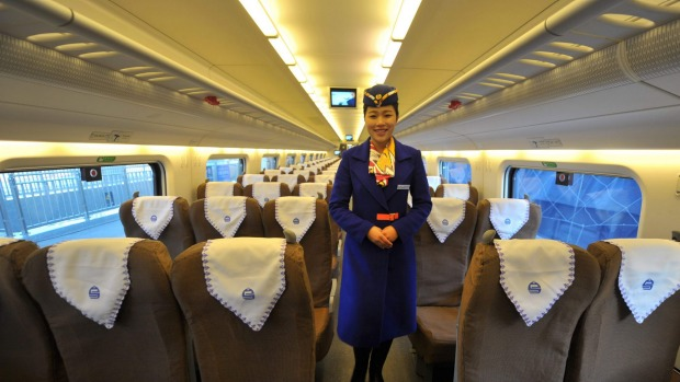 A train conductor stands in a cabin of a bullet train that will travel from Urumqi to Lanzhou at the Urumqi south ...