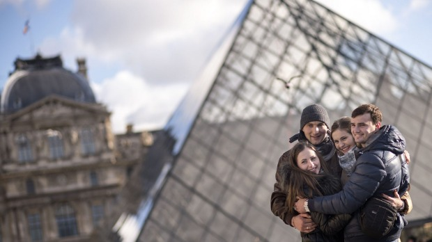 Tourists pose for a photo at the Louvre Pyramid in Paris.