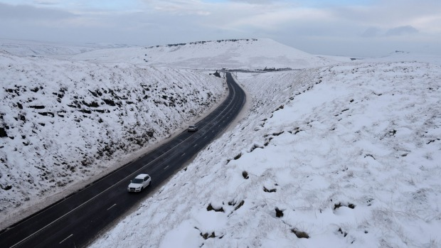 Cars travel along a gritted road between snow-covered fields near the village of Diggle, northern England.
