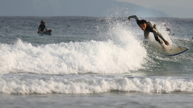 A surfer rides a wave at Shirahama Beach in Shimoda, Shizuoka Prefecture.  Shimoda is located southwest of Tokyo and ...