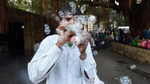An Indian youth selling a self-made soap bubble making device blows bubbles to attract tourists in front of the iconic ...